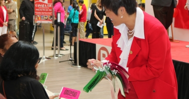 Soo Wong hands out Ontario 150 flags to audience